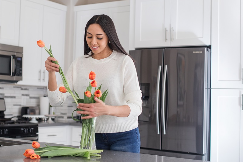 lady putting tulips in a vase