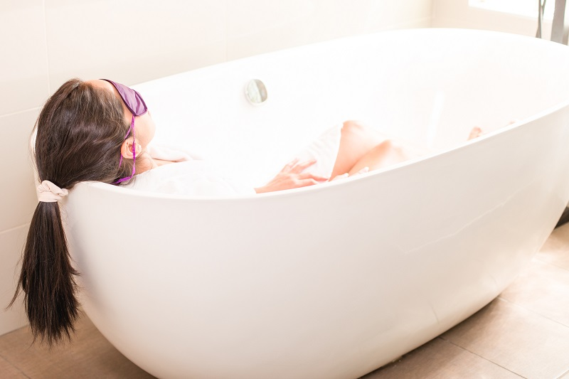 woman relaxing in bath with eye mask on