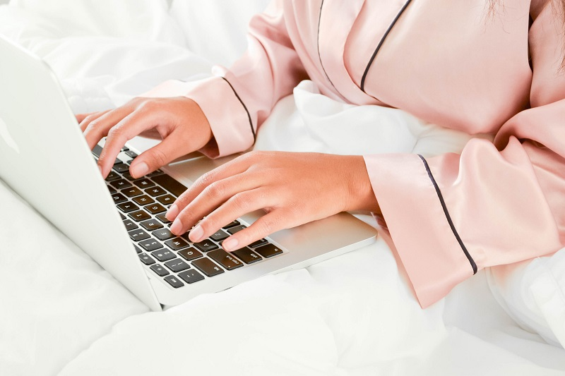 woman in pink pyjamas working on laptop in bed