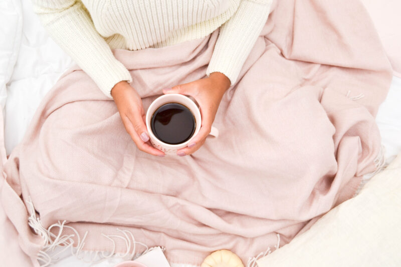lets get cozy woman under pink blanket holding a cup of tea