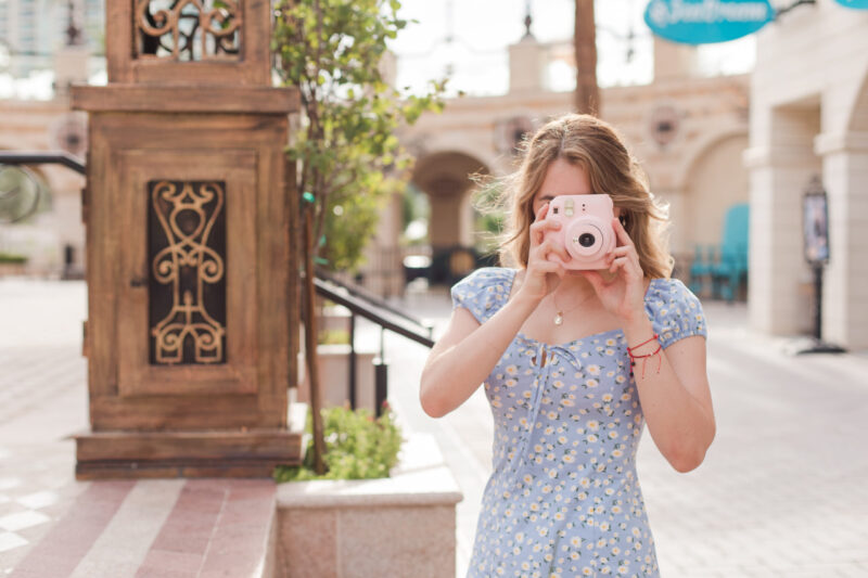 woman with a pink fujifilm camera